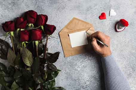 plan-the-perfect-valentines-day-man-hand-holding-pen-writing-love-letter-with-greeting-card